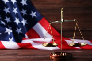 scales of justice and the Flag of the United States of America